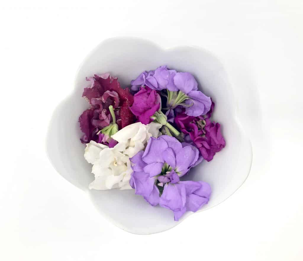 a variety pf edible flowers pictured in a bowl