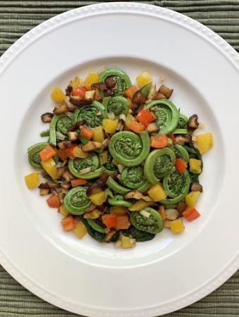 Fiddleheads & Ramps Sauté on a white plate over a sage green placemat