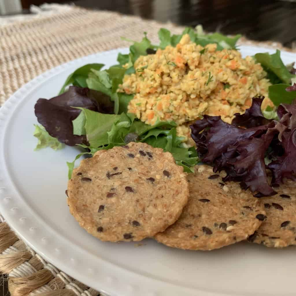 "Tempeh ""tuna"" salad placed on a bed of mixed greens with a side of 3 crackers"