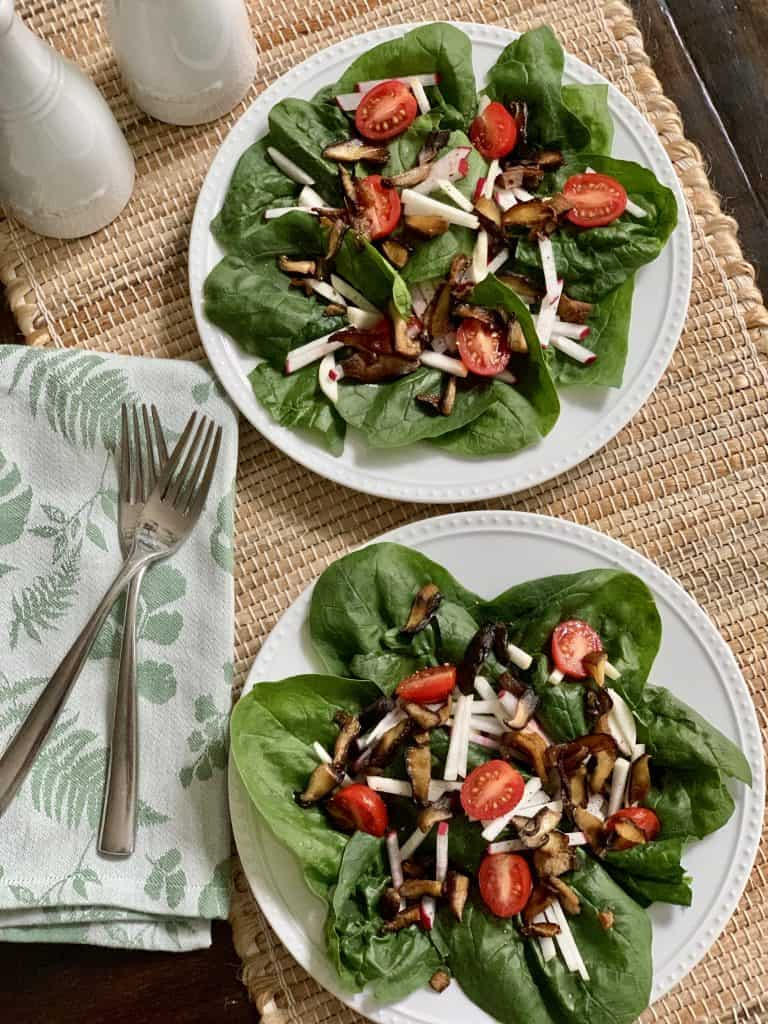 Spinach salad plated with roasted shitiake mushrooms, tomatoes, sliced radiahes & turnips