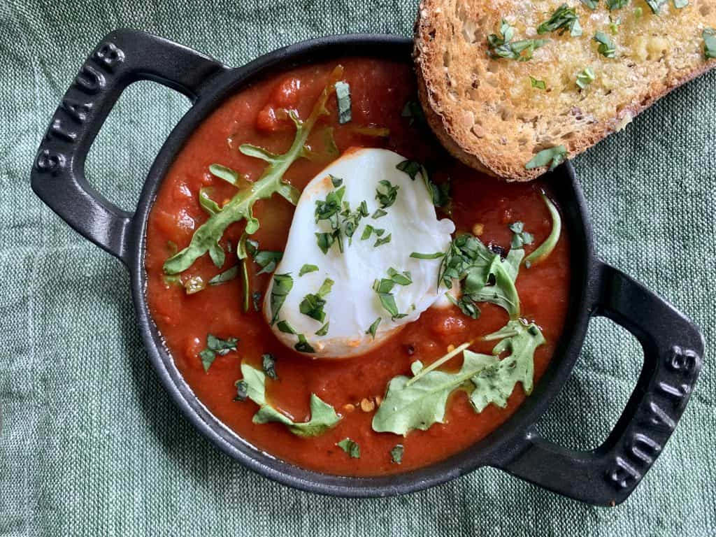 Shakshuka - placed in a cast iron skillet filled with jar sauce, a poached egg, and some greens with a slice of toasted bread topped with garlic oil and chopped basil