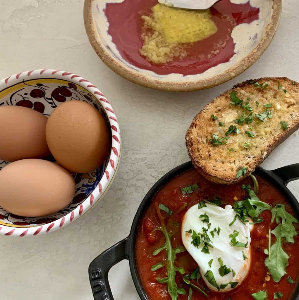 Shakshuka - placed in a cast iron skillet filled with jar sauce, a poached egg, and some greens with a slice of toasted bread topped with garlic oil and chopped basil. Also pictured 3 raw brown eggs in a bowl and a dish with fresh garlic oil