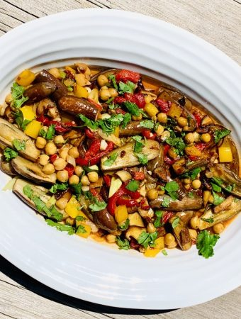 Fairy Tale Eggplant Sauté - a colorful mix of eggplant, red peppers, chick peas and spices cooked and displayed on a white serving platter with a wood background