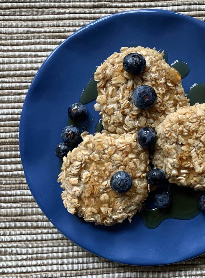 Pan Fried Overnight Oats on a blue plate with blueberries and maple syrup