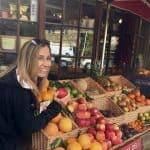 Chef Cindy picking an apple at a town market in the English countryside.
