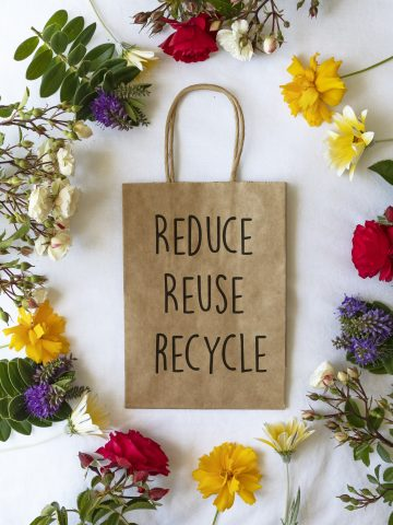 """Reduce Reuse Recycle"" text on a plain brown paper bag flat lay with bright colourful flowers - Retail spring shopping message concept"