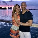 Chef Cindy pictured with her husband Rich and a colorful sky in Miami, waterside