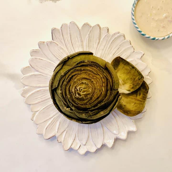 Steamed Artichoke with Yogurt Dipping Sauce on a beautiful white flower plate