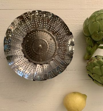 Artichoke pictured with steamer basket & lemon