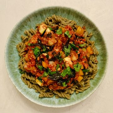 Veggie Tempeh Bolognese over mung bean pasta and topped with fresh basil.