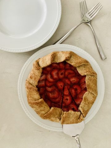 Vegan Strawberry Galette on a white plate with first slice cut into