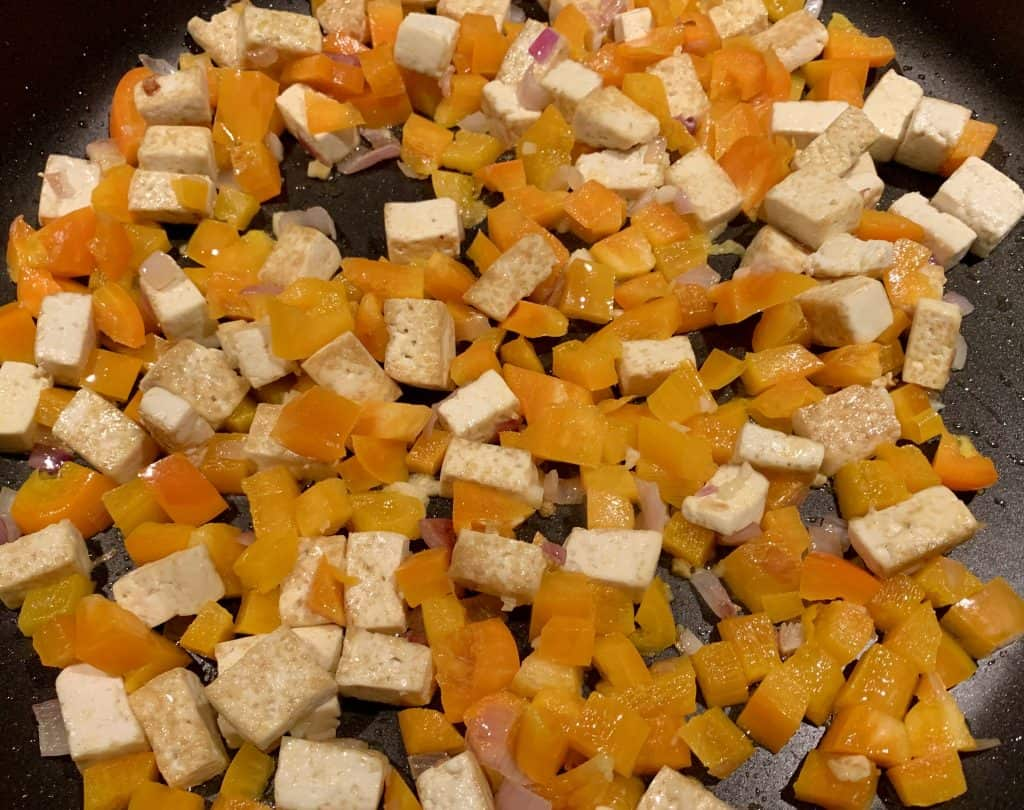 Tofu, yellow peppers, shallots and mango being heated in a non stick pan