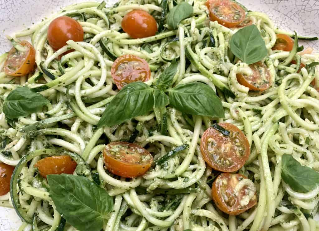 Pesto Zoodles and Tomato Salad pictured in a large serving bowl blended and topped with fresh basil leaves