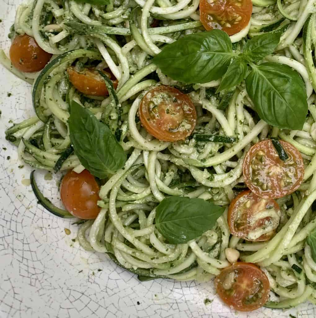 Pesto Zoodles and Tomato Salad cropped pictured blended and topped with fresh basil leaves