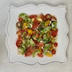 Assorted Garden Heirloom Tomato Basil Salad with Cippolini Onions on a decorative plate