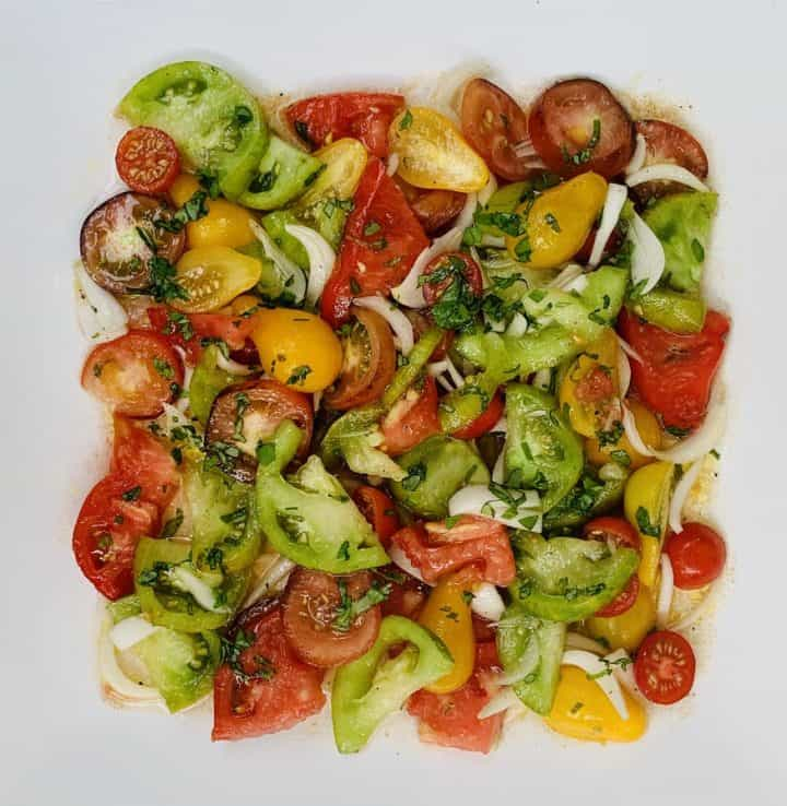 Assorted garden tomatoes mixed together in a salad and plated