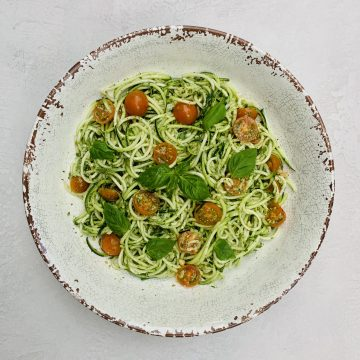 Pesto Zoodles and Tomato Salad pictured in a large serving bowl with pesto sauce in the middle and fresh basil leaves