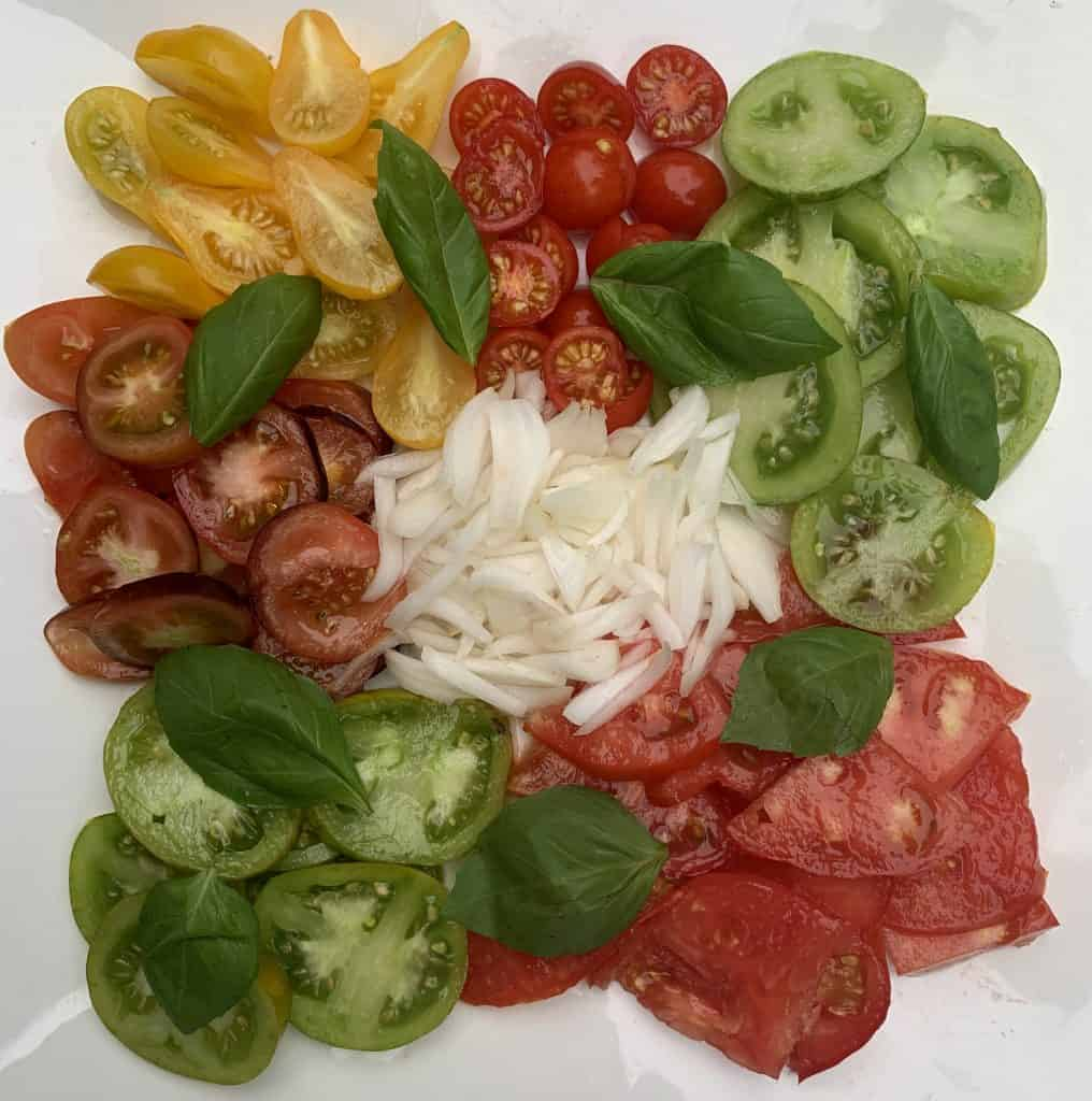 Garden tomatoes cut up an separated on a platter with cipollini onions and basil