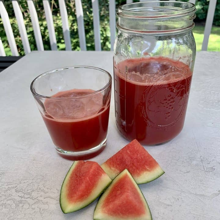 Jar of Watermelon Ginger Juice poured in a glass with watermelon wedges