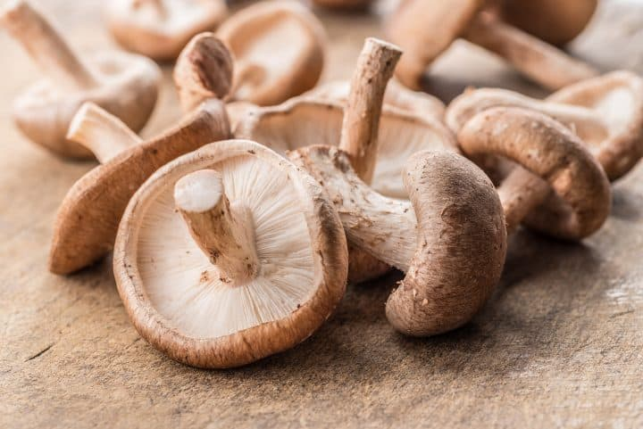 Shiitake mushrooms on a wooden background.