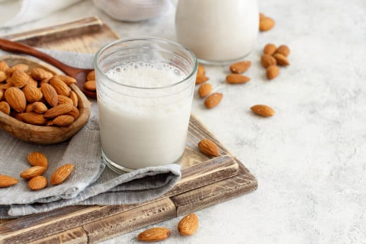 cup of freshly made almond with scattered almonds on the side