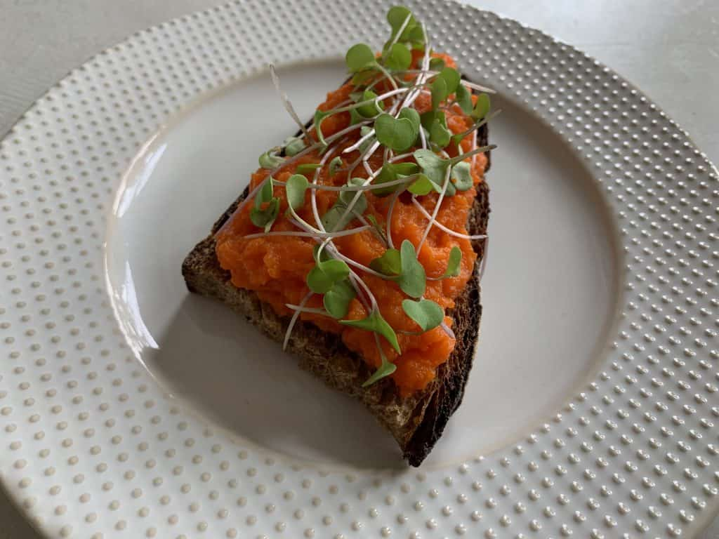 Steamed carrot mash on toast topped with microgreens