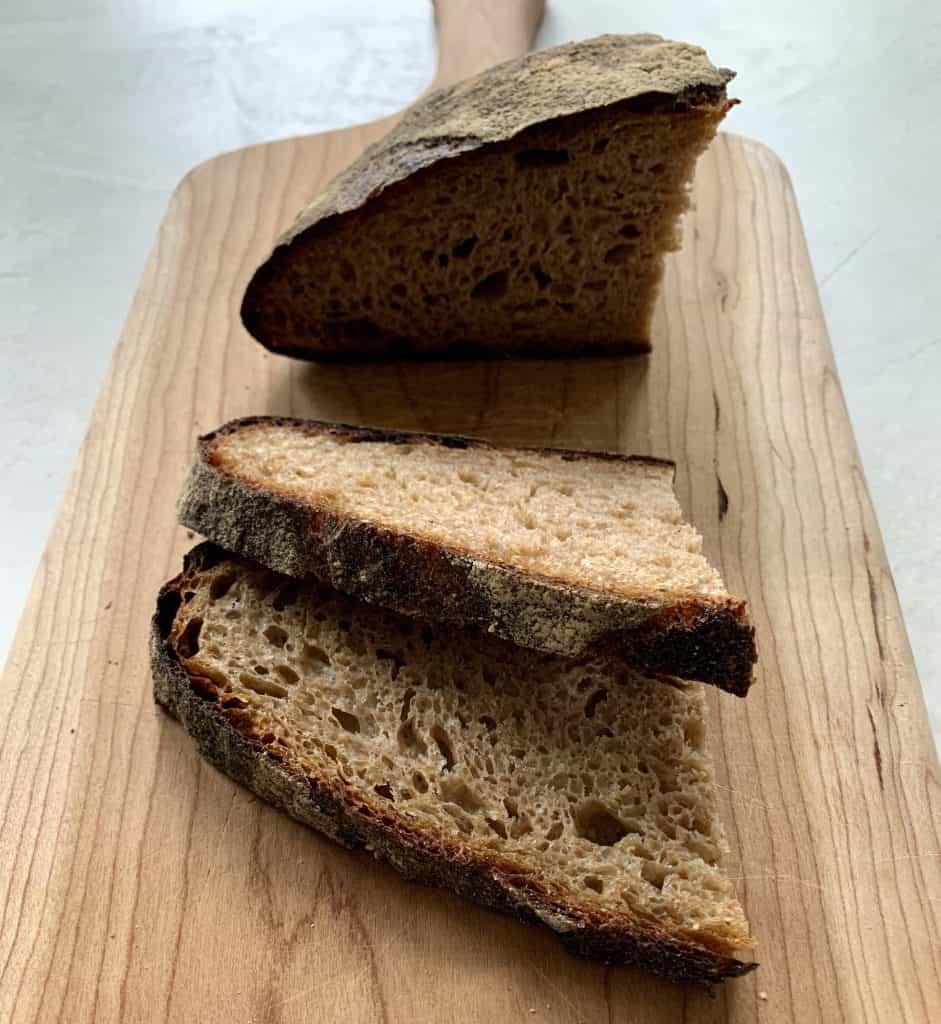 Fresh Bread sliced on wooden cutting board